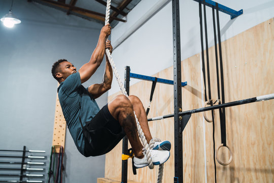 Athletic man doing climbing exercise.
