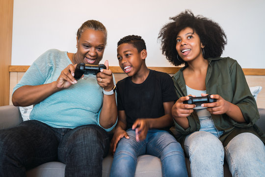 Grandmother, mother and son playing video games at home.