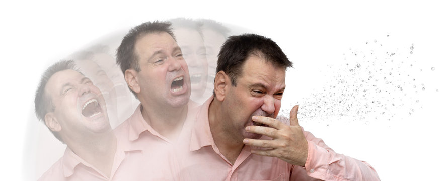 A man is coughs to his hand, isolated on a white background. A sick passenger sneezes bacilli and viruses around himself.