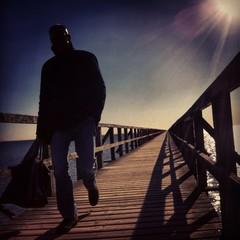 Full Length Of Man Walking On Wooden Pier