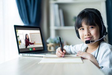 Homeschool Asian little young girl learning online class from school teacher by remote internet...