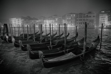 Gondolas Moored On Grand Canal By Illuminated City Against Sky At Night