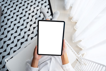 Top view mockup image of a woman holding black tablet pc with blank white desktop screen while...