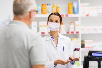 medicine, pharmaceutics, health care and people concept - apothecary wearing face protective medical mask for protection from virus disease showing drug to senior man customer at drugstore