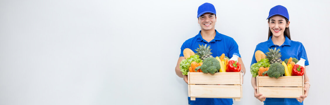 Closeup portrait of asian couple delivery man woman in blue uniform hold fresh grocery vegetables food isolated on white. Healthy lifestyle shopping internet online supermarket delivery teamwork