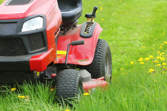 Mowing or cutting the long grass with a lawn mower . Gardening concept background