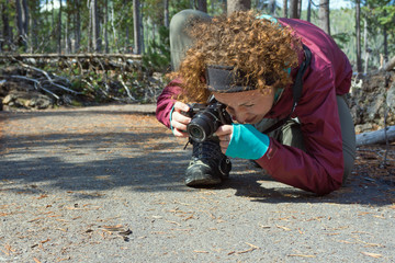 Behind the scenes photograph of a young, red-headed female photographer going low in an awkward position to shoot a small garter snake on a paved path in a wooded area on a cold sunny autumn day.