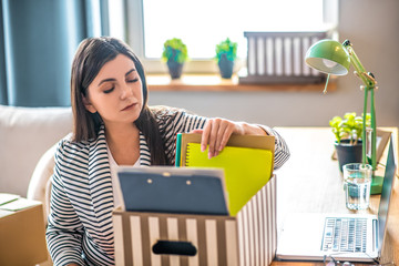 Young woman in a striped jacket packing documents and looking involved