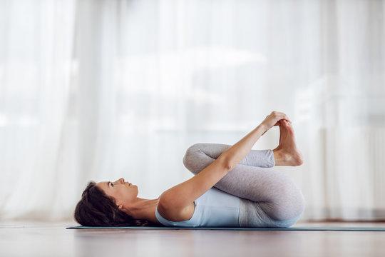 Side view of fit slim yogi girl in Happy Baby yoga pose. Yoga studio interior.