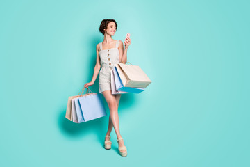 Full length body size view of her she nice attractive pretty cheerful cheery girl carrying new brandy things bag clothes using cell isolated on bright vivid shine vibrant blue color background