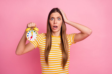 Close-up portrait of her she nice attractive lovely discontent worried girl holding in hands retro clock overtime loss omg isolated over pink pastel color background