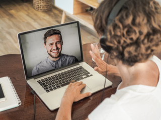 woman having a video conference call with a man waving into her laptop wearing a headset with notepad and mobile phone on the desk in her home office