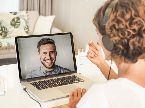woman having a video conference call with a man on her laptop wearing a headset with notepad and mobile phone on the desk in her home office