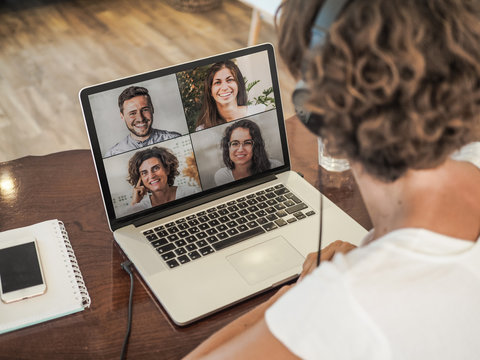 woman having a video conference call with four people at her laptop wearing a headset with notepad and mobile phone on the desk in her home office