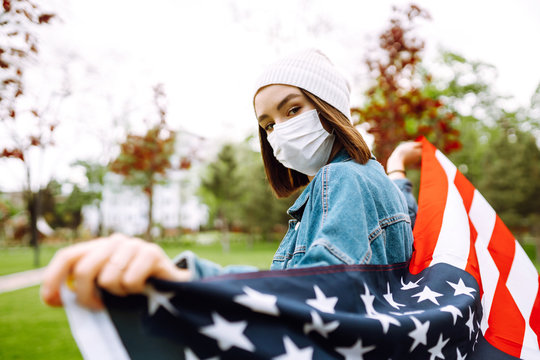 Young girl in a protective mask with the flag of America. Independence Day of America. 4th of July. Coronavirus in America. The concept of preventing the spread of the epidemic.