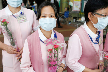 Nurses receive flowers and pose for a photo to celebrate International Nurse day in Taipei