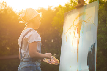 A young woman artist holds a brush and paints a picture on an easel in the rays of the sunset. The...