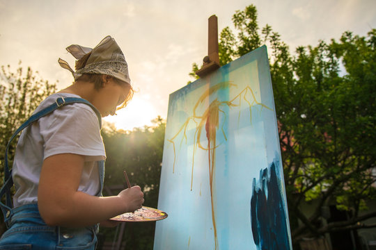 A young woman artist holds a brush and paints a picture on an easel in the rays of the sunset. The painter paints oil paintings in the garden