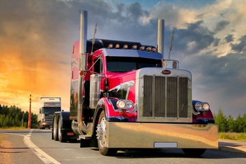 American Show Truck Tractor Peterbilt 379 trucking along highway against Sunset Sky. Illustrative Editorial Content.