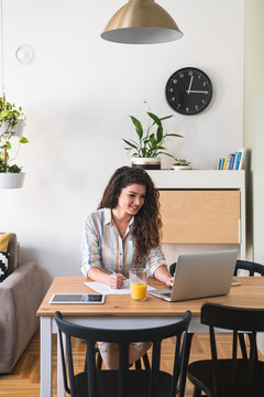 Woman working on laptop computer from home stock photo