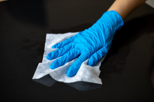 Woman cleaning home office table surface with wet wipes in blue gloves stock photo