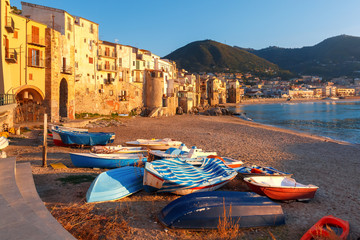 Fototapete - Boats on the beach and sunny houses in coastal city Cefalu at sunset, Sicily, Italy