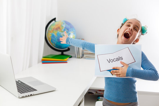 Little girl at speech therapist office, little girl learns vocal on laptop online, distance learning