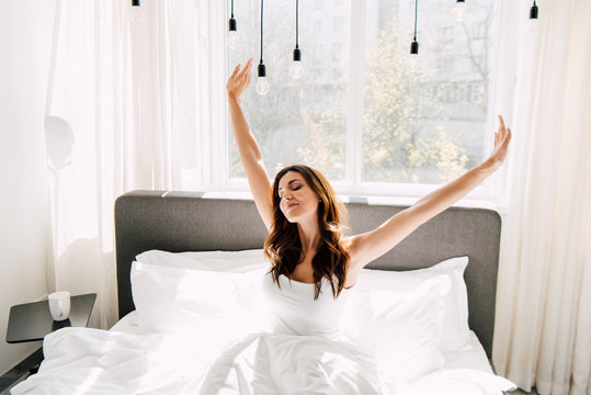 attractive happy woman stretching on bed in morning during quarantine