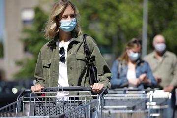 Menschen mit Mundschutz stehen mit einem Einkaufswagen in einer Warteschlange