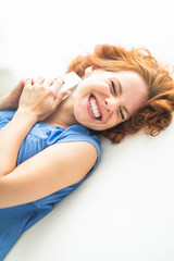 woman lying on bed with smartphone smiling
