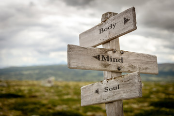 body mind soul text engraved on old wooden signpost outdoors in nature. Quotes, words and illustration concept. Wall mural