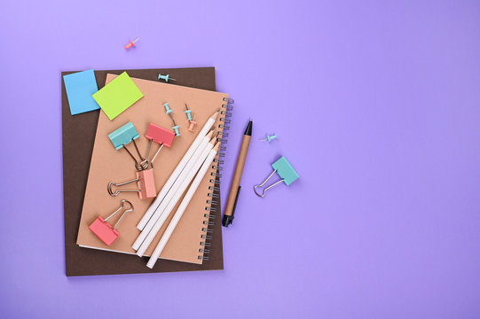 Stationery items, multi-colored for study and work in the office on a bright lilac background. The concept of returning to school and to work after quarantine. Top view, free space for text. Flat lay