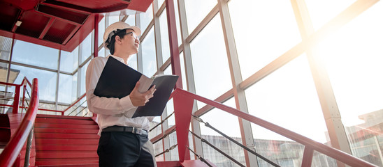 Asian civil engineer or construction worker man wearing protective safety helmet holding document file. Male architect working on red stair at construction site. Building and architecture concept