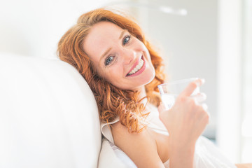 Young beautiful red-haired woman laughs happily at the camera and drinks a glass of water