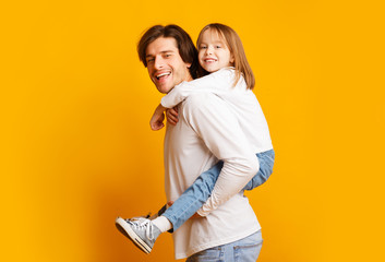 Positive family having fun over yellow background