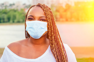Smiling afro american woman in medical mask looking at camera autumn evening spring in the park by...