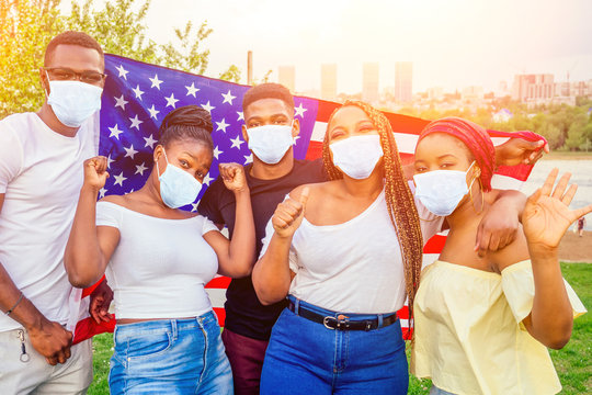 Group of girls and boys in medical mask smiling with American flag in spring park autumn evening learning English language exchange students