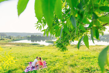 Fototapeta girl and guy kissing on a picnic. beautiful meadow by the lake a