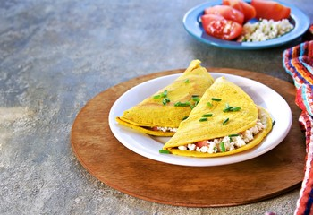 Chilla, tortillas or pancakes made from chickpea flour stuffed with cheese panir and tomato on a white plate on a gray concrete background. Indian food, street food. Vegetarian recipes.