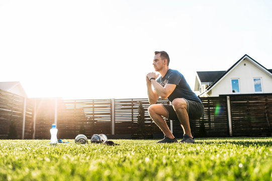 A guy is doing squats in the backyard. Sports training at home, workout outdoors