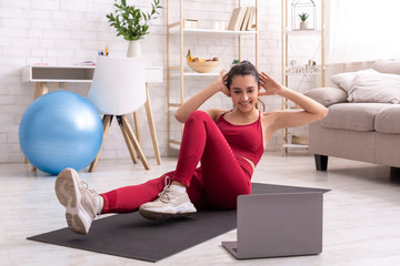 Latin girl exercising to live bodyweight workout on laptop, doing abs exercise at home