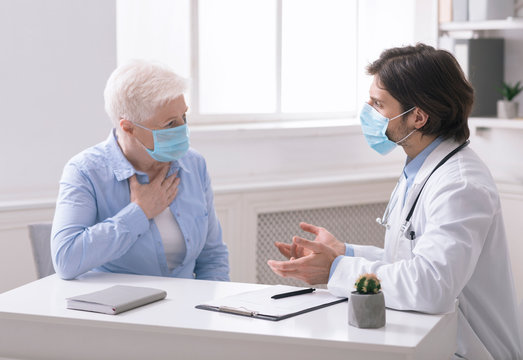 Doctor consulting senior woman with cough, in office