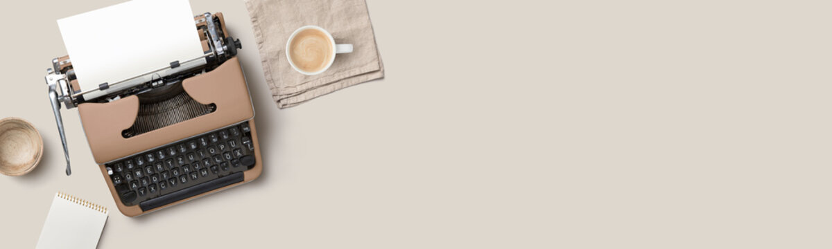 writing themed conceptual home office banner or header with mocca colored / brown vintage / retro typewriter on a beige desk - flat lay / top view