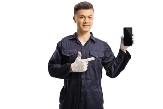 Young mechanic holding a mobile phone and pointing