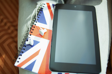 Closeup on tablet PC, headphones and UK flag notebook