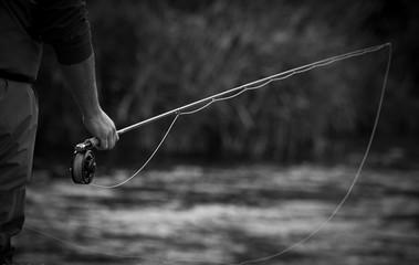 Obraz Close-up Of Man Holding Fishing Rod By River - fototapety do salonu