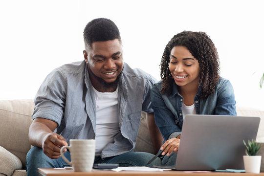 Young african american couple planning budget together at home, writing notes to notebook, creating checklist for shopping or guest list for wedding