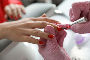 Professional manicurist applying polish on client's nails in beauty salon, closeup
