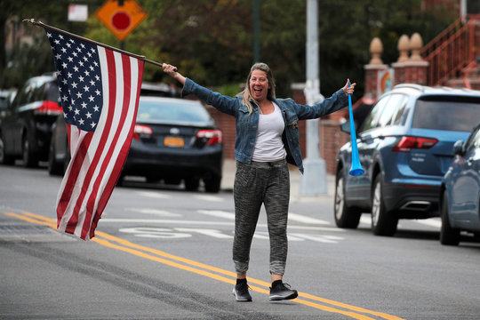 A woman waves a flag in the street during the nightly clap and cheer for healthcare workers, during the outbreak of the coronavirus disease (COVID-19), in Brooklyn, New York