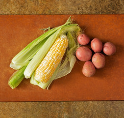 A Husked Ear of Corn and Red Potatoes on a Cutting Board in Natural Lighting